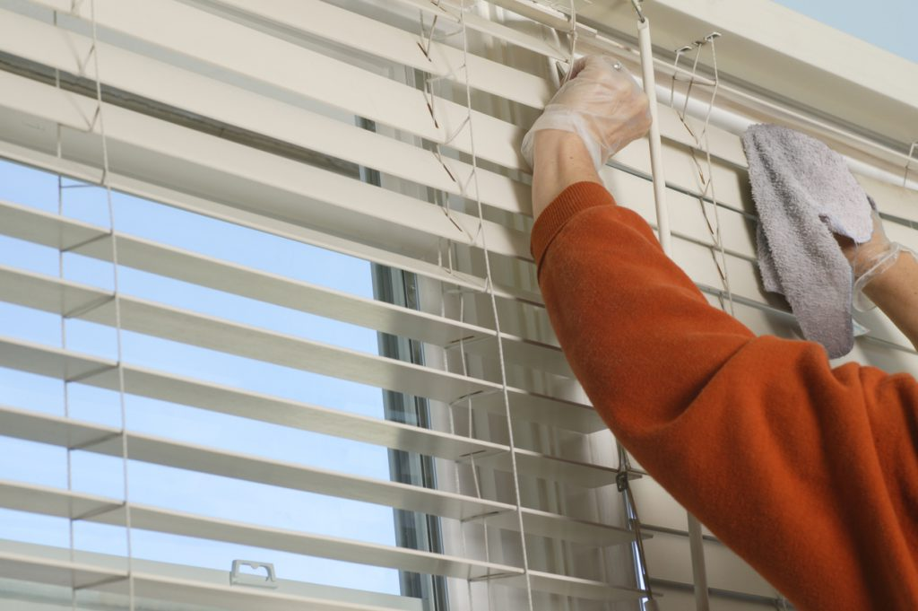 Woman cleaning wooden venetian window blinds with dust rag